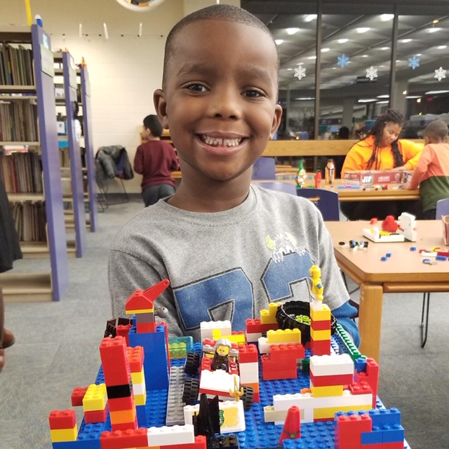 boy smiling and displaying his lego creation