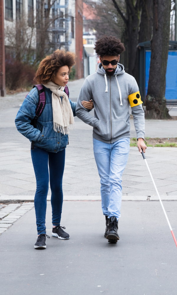 young couple, woman with man using a white cane, crossing the street